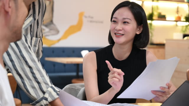 Cheerful young businesswoman discussing with coworkers