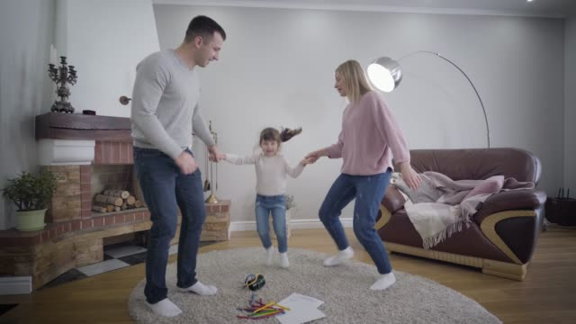 Cheerful young Caucasian family having fun indoors. Mother and father holding daughter's hands, dancing and raising child up. Lifestyle, leisure, enjoyment.