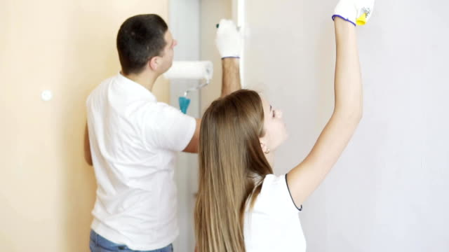 Cheerful young couple in white shirts decorate their new apartment. Young husband and wife are painting the wall using paint rollers. Beautiful couple making repairs in their new flat. video