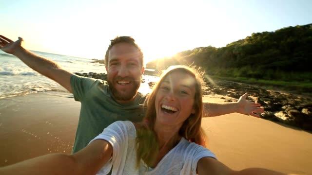 ビーチで陽気な若いカップルは、selfie の肖像画を取る - セルフィー点の映像素材/bロール