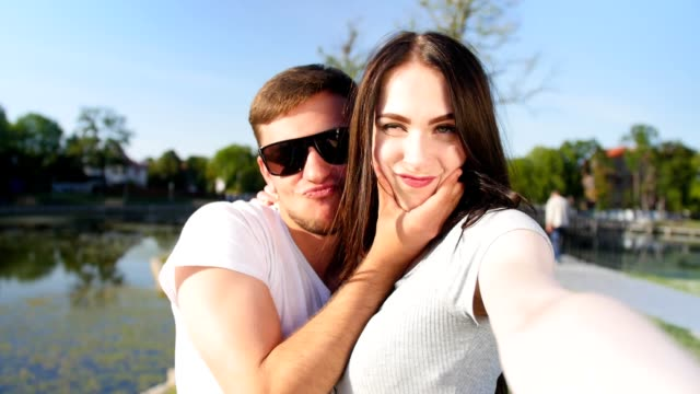 Cheerful young couple take a selfie portrait in the park. Happy together. Close up shot.