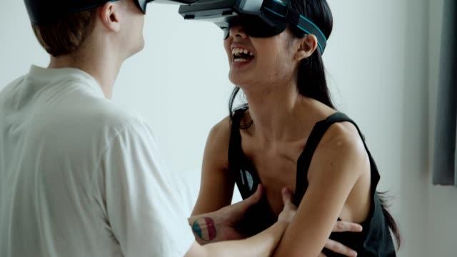 vr 3-d gözlük kullanarak neşeli genç çift - sanal gerçeklik stok videoları ve detay görüntü çekimi