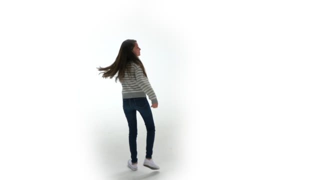 Cheerful young girl at a studio with white background dancing while facing camera smiling