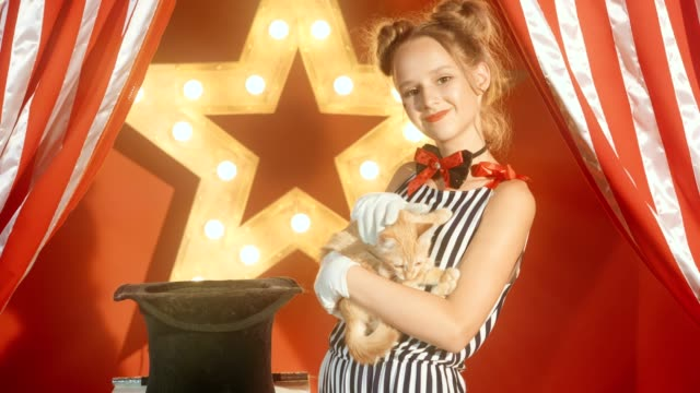 Cheerful young girl magician is holding kitten in hands video