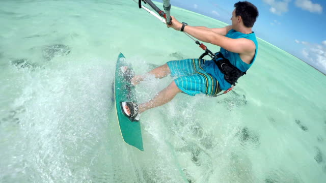 CLOSE UP: Cheerful young kitesurfer kiting in perfect blue lagoon on Zanzibar video