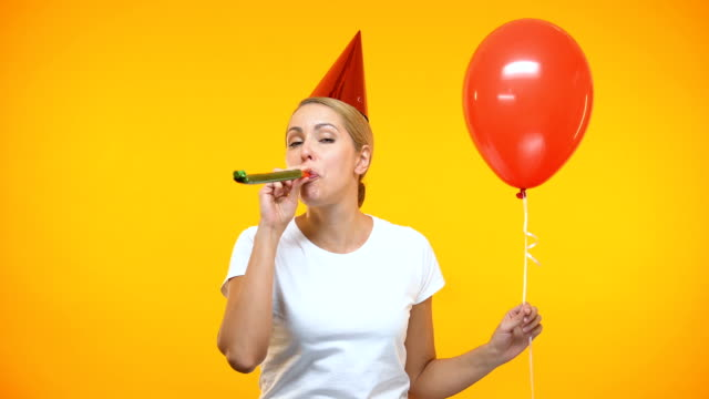 Cheerful young lady in party hat blowing horn, holding red balloon, birthday video