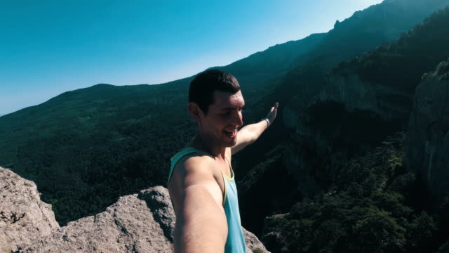 Cheerful young man raising his hands high on top of the big rocky mountain with Cross