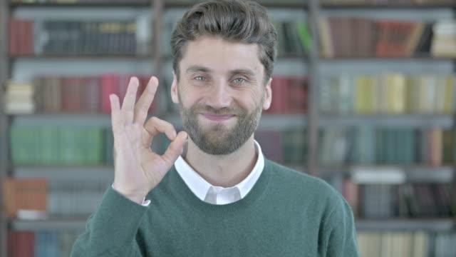 giovane allegro che mostra un segno ok - arto umano video stock e b–roll