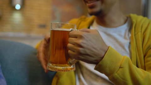 giovane allegro che parla e beve birra, divertendosi con gli amici alla festa - bere video stock e b–roll