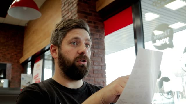 A cheerful, young man with a beard reads the menu and makes an order at the bar Happy, young man with a beard having fun talking, reading the menu and making an order in a cafe menu stock videos & royalty-free footage