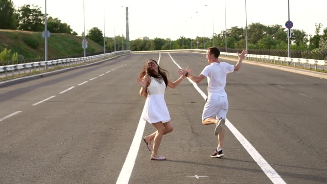 Cheerful young people dancing on an empty road.
