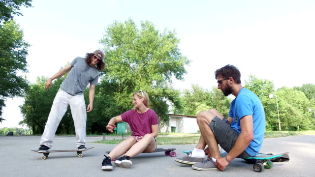 Cheerful young skateboarders chilling and doing tricks on skateboard video