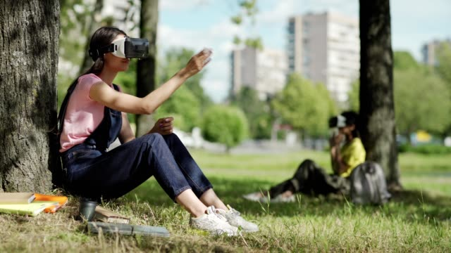 Cheerful young student in VR headset enjoying listening music and relaxing after studying leaning on tree trunk in park. Another student wearing virtual reality glasses in background