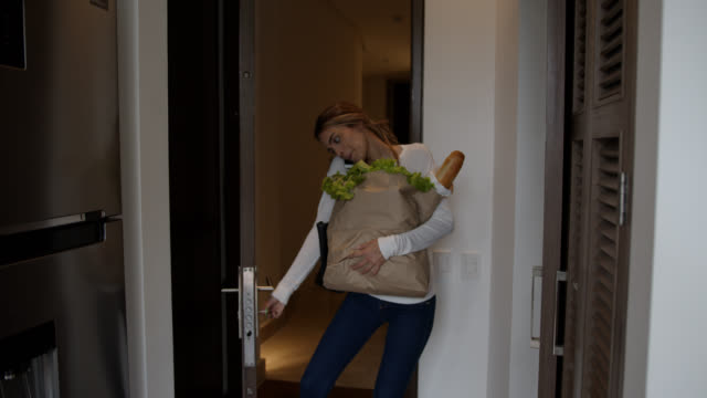 Cheerful young woman arriving home carrying groceries talking on the phone and opening the door