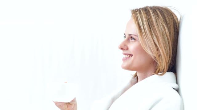 vidéos et rushes de bonne humeur jeune femme appréciant une boisson chaude au spa - peignoir