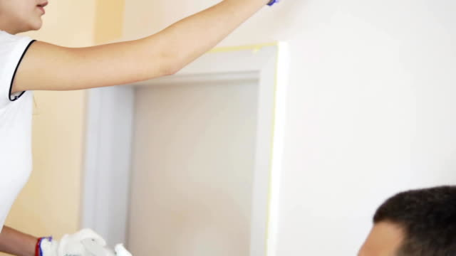 Cheerful young woman in white shirt painting the wall in white color using a brush. Young husband is helping video