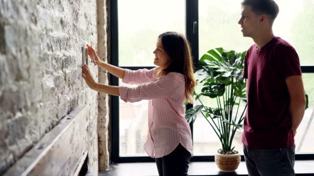 glad ung kvinna är att välja plats för inramade fotografi på tegelvägg medan maken hjälper henne, lyckliga paret talar och fattar beslut. - hänga bildbanksvideor och videomaterial från bakom kulisserna