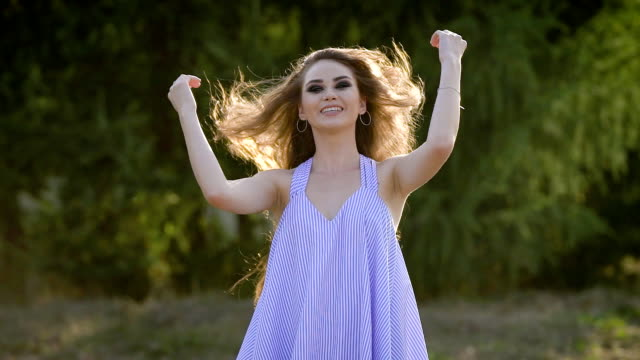 cheerful young woman is posing for a camera in summer day on background of green trees, touching hair and smiling video