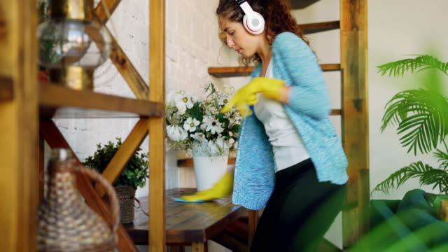 cheerful young woman is washing the table at home, listening to music with headphones, singing and dancing. girl is using wet cloth and rubber gloves. - stay at home parent stock videos & royalty-free footage