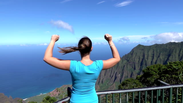 SLOW MOTION: Cheerful young woman on lookout point raising arms victoriously video