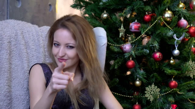 Cheerful young woman pointing finger at camera on christmas tree background video