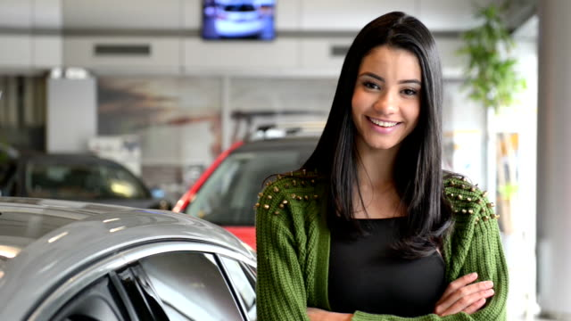Cheerful young woman posing in a car dealership Cheerful young woman posing in a car dealership. saleswoman stock videos & royalty-free footage