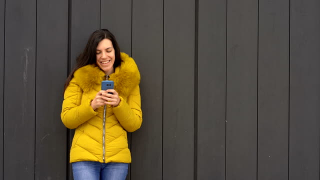 Cheerful young woman with mobile phone