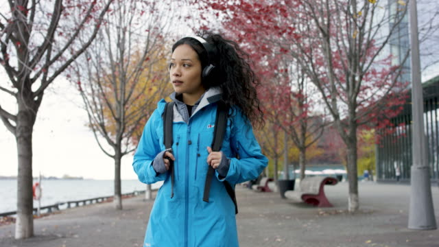 A cheerful young women is walking down a path during fall and fixing her hair. video