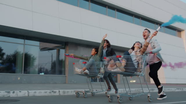 Cheerful youth riding shopping carts in city street holding smoke flares Cheerful youth men and women are riding shopping carts in city street holding smoke flares laughing enjoying leisure time. Freedom and friendship concept. woman pushing cart stock videos & royalty-free footage
