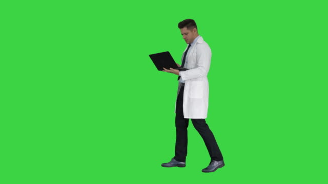 Cheerfull doctor with laptop laughing after giving a serious look to camera on a Green Screen, Chroma Key
