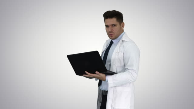 Cheerfull doctor with laptop laughing after giving a serious look to camera on gradient background