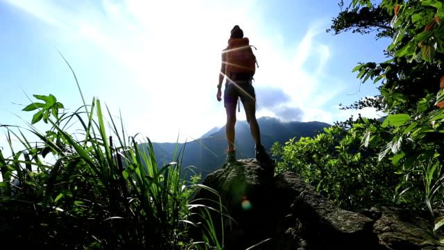 tifo donna hiking le braccia aperte in cima alla montagna roccia - cultura coreana video stock e b–roll