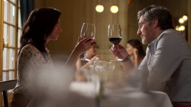 Cheers to love! Couple in restaurant romance stock videos & royalty-free footage