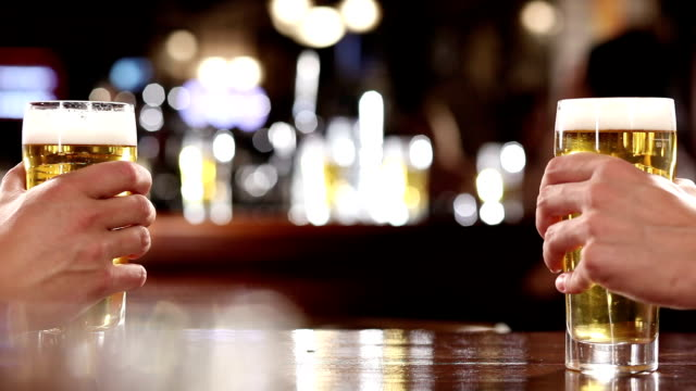 Cheers! Hands of two men holding beer celebratory toast stock videos & royalty-free footage