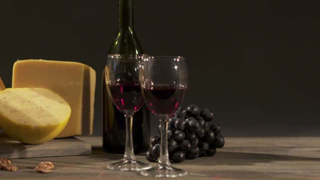 Cheese and wine on a dark background. Different types of cheese video