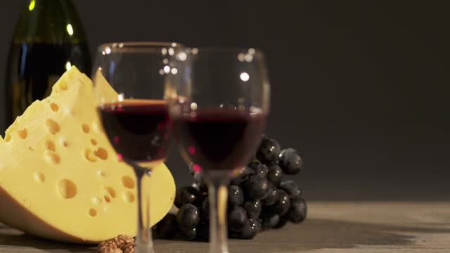 Cheese and wine tasting. Two glasses with red wine, grapes and cheese skewers