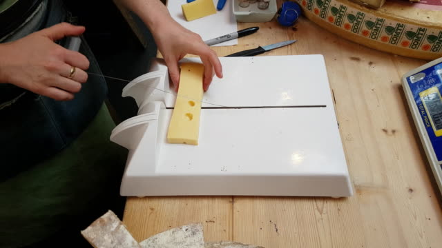 cheese being cut on food market - formaggio comté video stock e b–roll