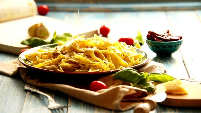 vidéos et rushes de fromage est être râpé sur le plat de pâtes italiennes fraîchement cuite - parmesan