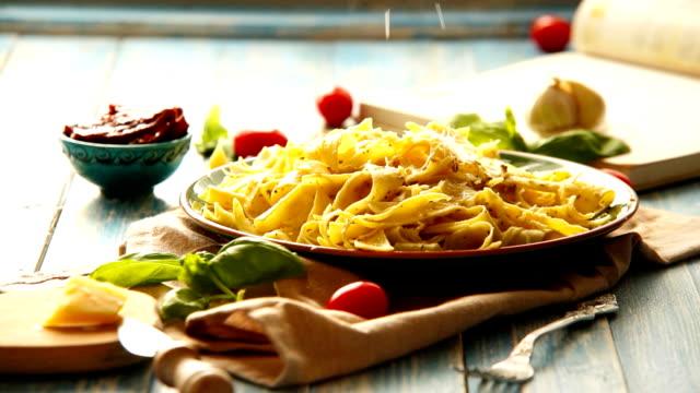 käse ist auf dem teller frisch zubereiteten italienischen pappardelle pasta gerieben wird. sonnigen tag hintergrundbeleuchtung video. - pasta stock-videos und b-roll-filmmaterial