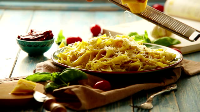 Cheese is being grated on the plate of freshly-cooked Italian pasta video