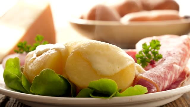 vidéos et rushes de raclette au fromage avec pommes de terre et salami - raclette