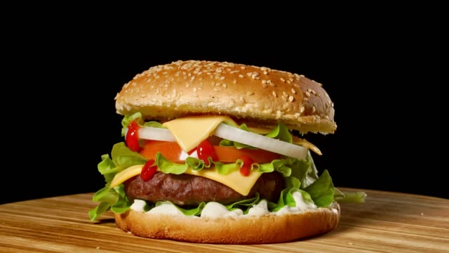 cheeseburger with bacon on a dark background. close-up. macro shooting - cheeseburger filmów i materiałów b-roll