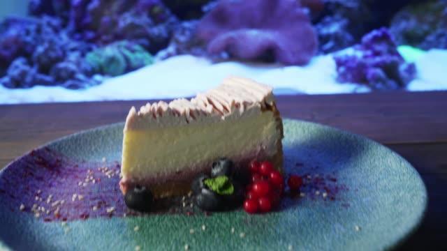 Cheesecake with berries on near aquarium.