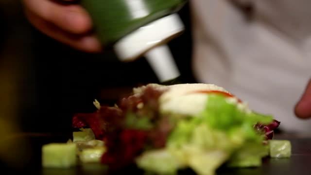 chef add sauce to salad video