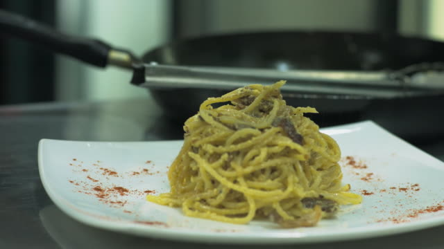 vidéos et rushes de chef, ajout de poivre ou épices à pâtes italiennes ou spaghetti sur assiette - spaghetti bolognaise