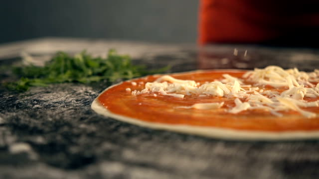 Chef adds cheese to pizza. Slow Motion video