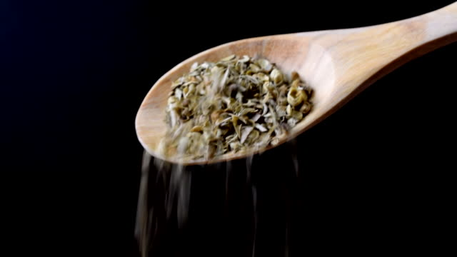 vidéos et rushes de chef ajoute origan sec de cuillère en bois pour le plat - plante aromatique