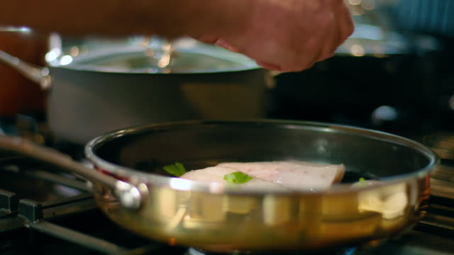 Chef adds herbs to fish fillets in frying pan