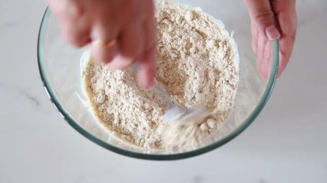 vídeos de stock, filmes e b-roll de o cozinheiro chefe adiciona a farinha da aveia aos ingredientes líquidos - sem glúten