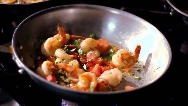 vídeos de stock, filmes e b-roll de um chef adiciona temperos a uma frigideira. - comida italiana